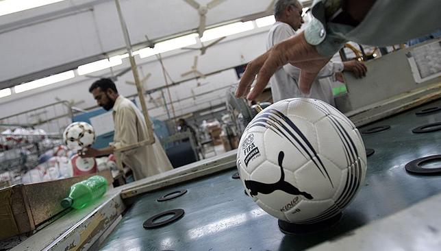 Les travailleurs effectuent des inspections de contrôle de la qualité à l'usine de football Saga à Sialkot, au Pakistan.