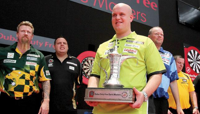 Man to beat: Michael van Gerwen shows off the trophy he won last year.