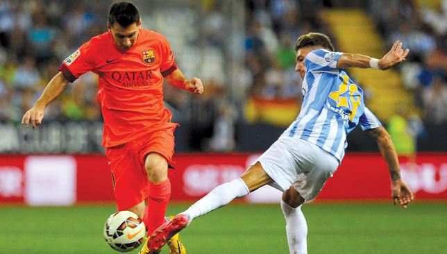 Going toe-to-toe: Malaga midfielder Samuel Castillejo challenges Lionel Messi.