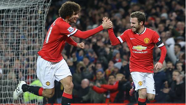 Juan Mata and Marouane Fellaini celebrate after combining to score Manchester United's first goal against Cambridge United in the FA Cup.