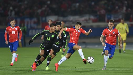 Sanchez (c) takes on the Mexico defence.