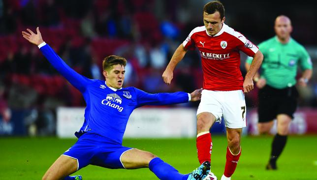 Stay right where you are: John Stones tackles Barnsley's Josh Scowen.